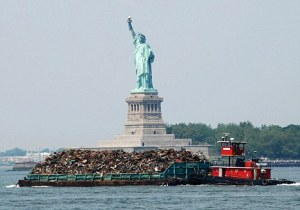 A tug boat pushes a garbage barge past the Statue of Liberty